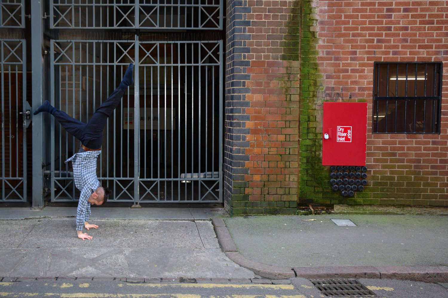 Ian Dolan, man contemporary dancing in the street in front of a gate