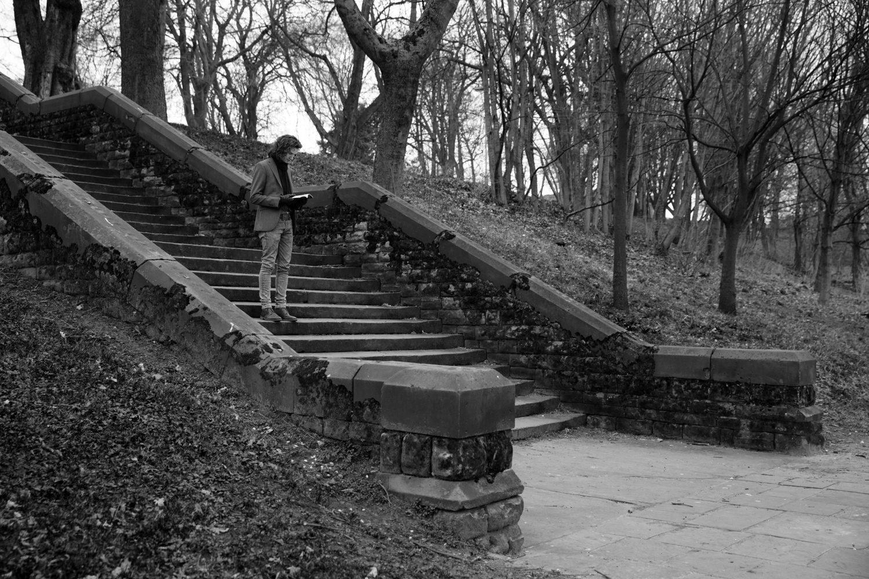 B&W Black and white stairs outside park man long hair books performance art live art