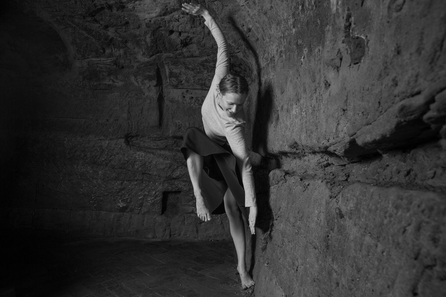 Black and white picture of Amy Harris dancing in the caves of the Maltcross in Nottingham