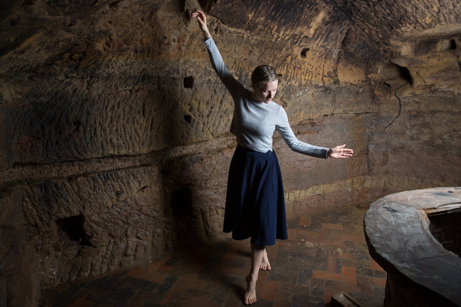 Amy Harris with her arms outstretched, dancing in the caves of the Maltcross in Nottingham