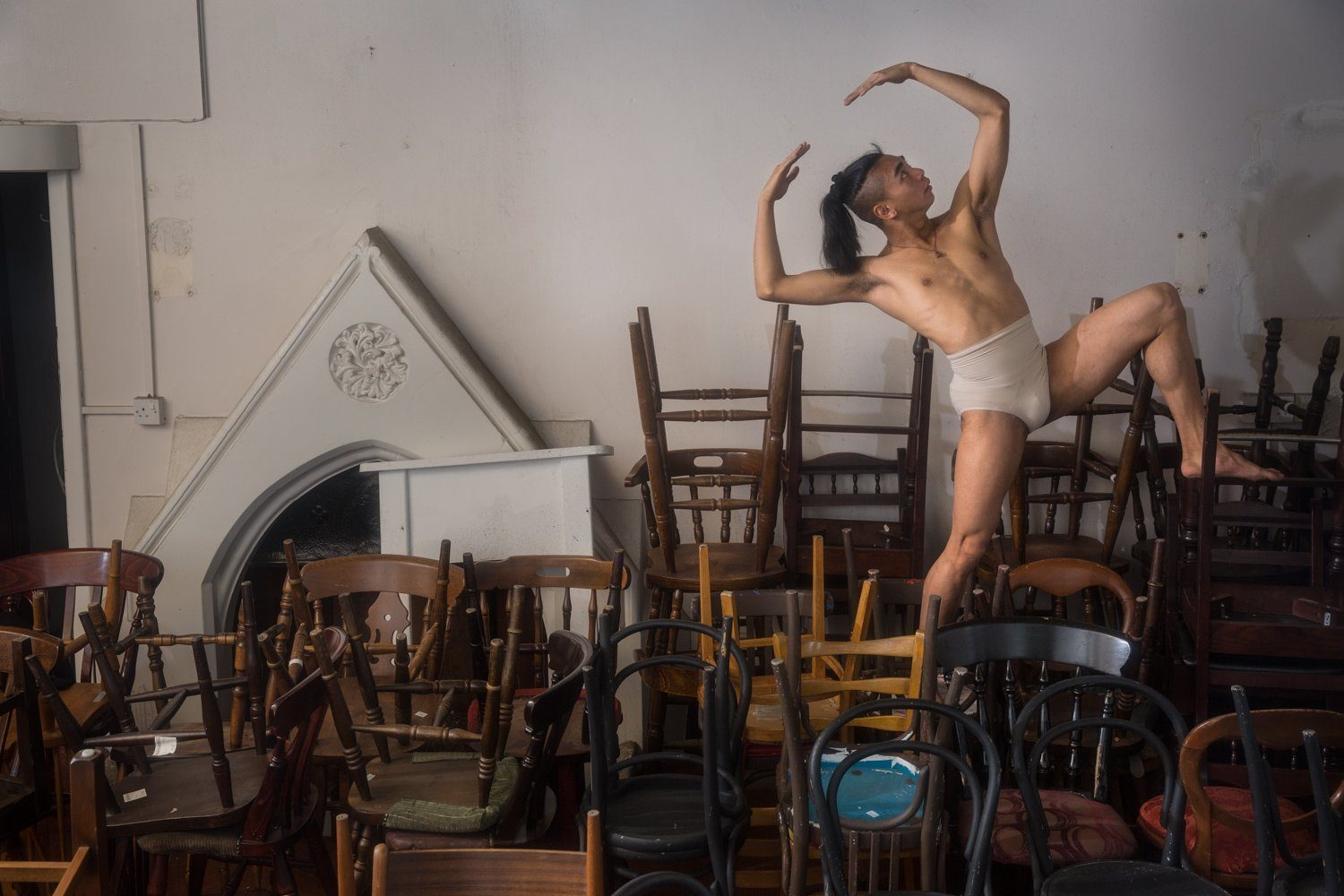 Mac Daniel Villanueva Palima dancing with chairs in Derby Theatre's Green Lane rehearsal rooms