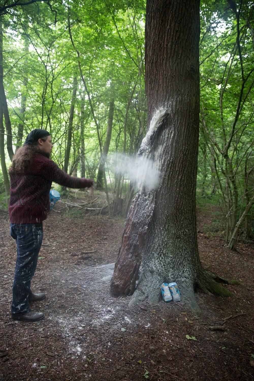 Matt Smith throws flour at a branch placed against a tree