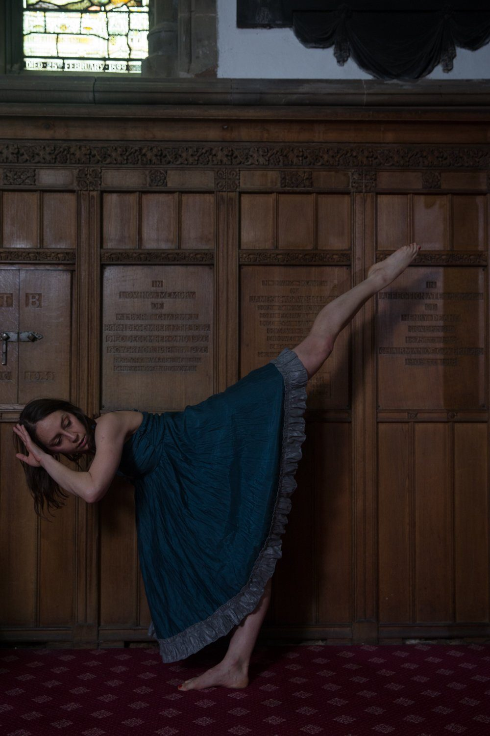 Giada dancing with her leg high in the air against a wooden wall