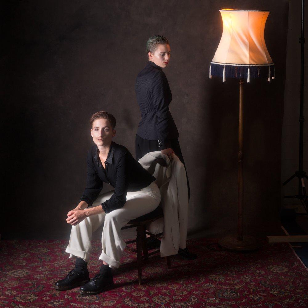 Portrait of Danni Spooner standing, looking away & Carise ZM sitting